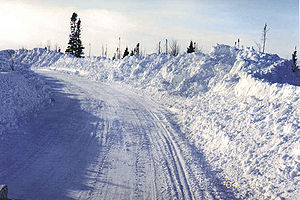 Photo showing Snow plowed and piled on road
