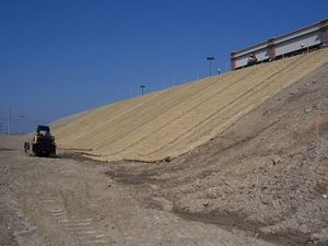 This picture shows an erosion control blankets being installed along a steep slope
