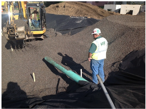 This picture shows a Infiltration media being placed in infiltration area with tracked backhoe