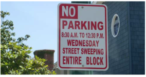 This image shows a no parking for street sweeping sign