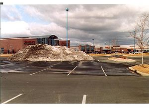 Photo showing Snow plowed and piled in parking lot